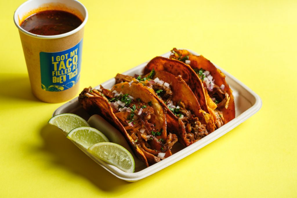 A tray of 3 Birria slow cooked beef tacos, with slices of lime and a cup of dipping broth