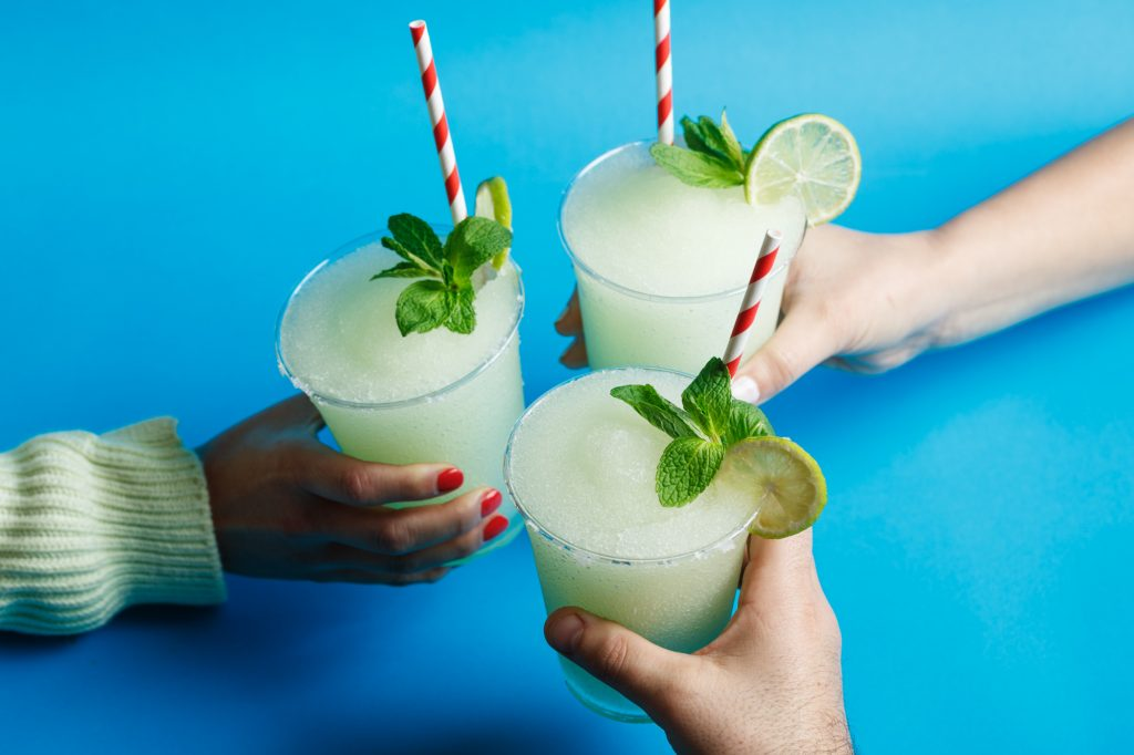 Three frozen margaritas with colourful straws