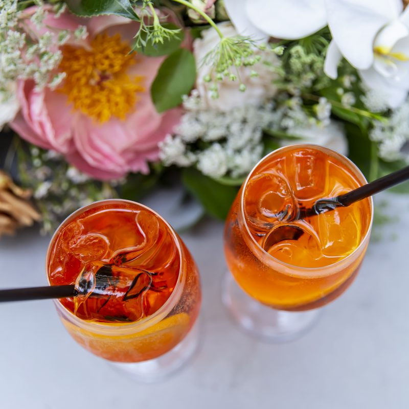 Aperol Spritz cocktails next to fresh flowers at QBF Eatery